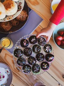 afternoon tea with kids small hand grabbing chocolate cupcake not just a tit lifestyle blogger flat lay